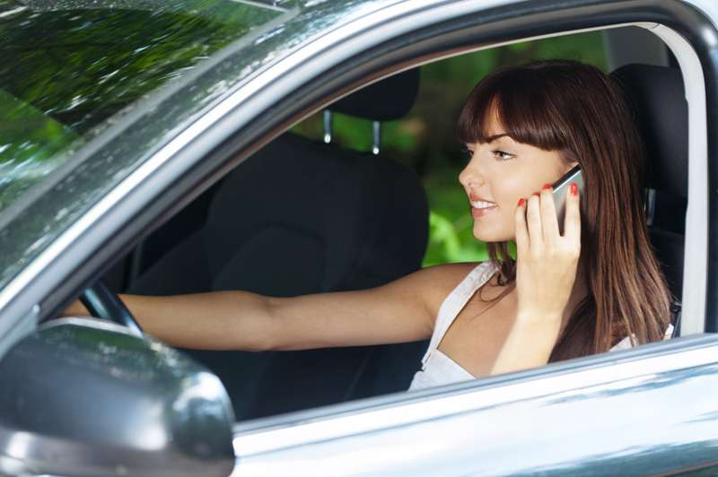 Young woman sitting car talking phone