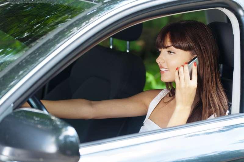 Young woman sitting car talking phone