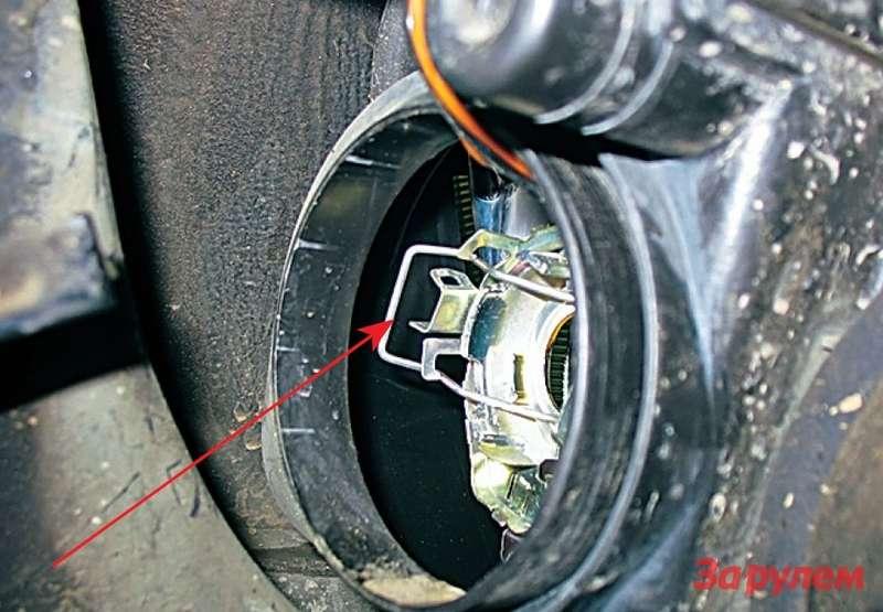 Из-за ненадежной фиксации скобы лампы Н4«Приоры» эту железку (стрелка) ничего не стоит обронить. Хорошо, если наземлю, ночаще она проваливается внутрь фары.