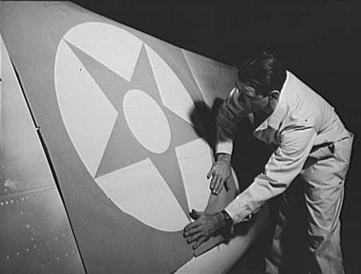 Рабочий кузовостроительного предприятия Briggs Manufacturing Company наклеивает знаки отличия накрыло бомбардировщика