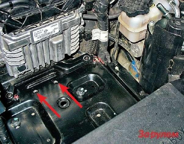 Длядоступа ктопливному фильтру снимаем аккумулятор. Крепление последнего неудачное: сложно подобраться кболтам прижимной пластины (отверстия показаны стрелками), мешает блок управления двигателем.
