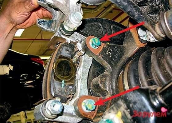 Hyundai Tucson: Задний тормоз— длядоступа кколодкам ручника снимаем скобу, вывернув ключом «на14» два болта еекрепления (стрелки). Удобнее использовать многогранный накидной ключ.