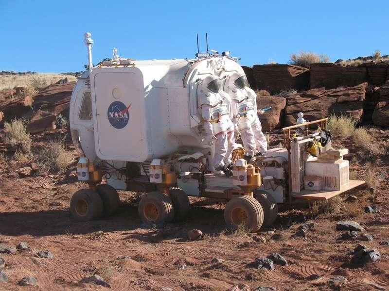 Сегодня NASA продолжает разработки «космических автомобилей» длямиссии наМарс 2020 года. Впустыни Аризона прошел испытание образец 12-колесного транспортера Small Pressurised Rover Concept, накотором установлена капсула, внутри которой двое астронавтов могут отдыхать после смены. Транспортер передвигатеся соскоростью 13км/ч иможет наодной зарядке батарей преодолеть порядка 1000км.