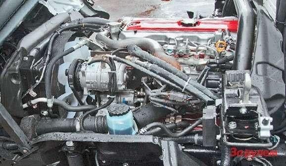С левой стороны двигателя установлен  компрессор кондиционера