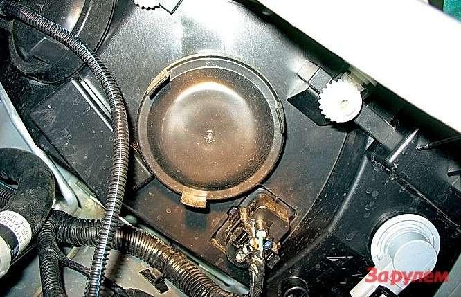 «Лада-Калина» При снятом бачке доступ к тыльной части фары просто отличный. Патрон поворотника белеет в правом нижнем углу.