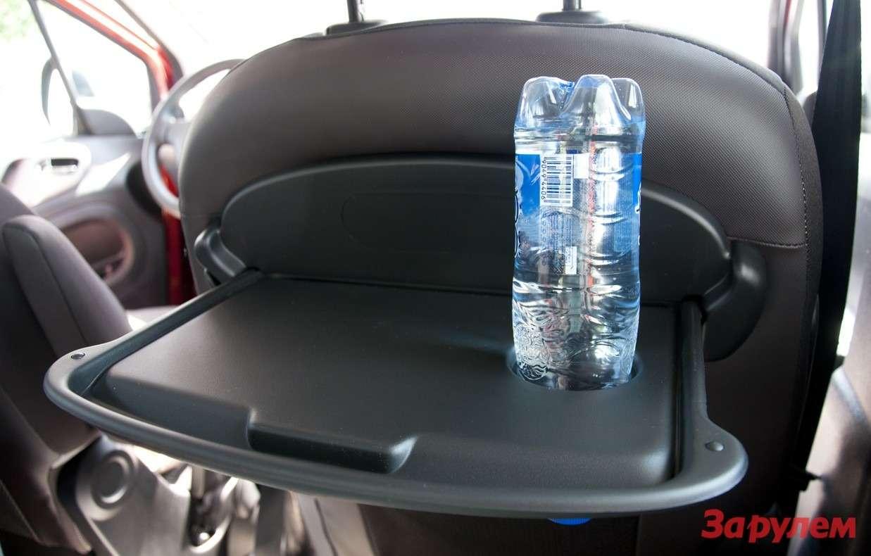 Откидной столик вспинке переднего сидения. Банку сэнергетиком не поставить— слишком широкое отверстие.