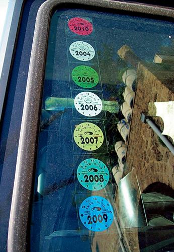 Гирлянда изстикеров технического осмотра наветровом стекле. Главное— чтобы не мешали обзору.
