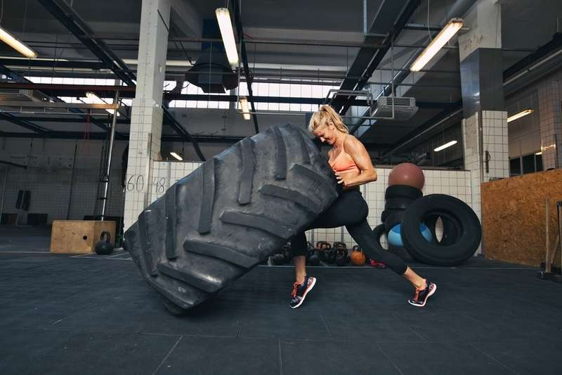 Crossfit woman flipping ahuge tire atgym