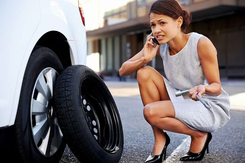 Woman calling for assistance with flat tire oncar inthe city