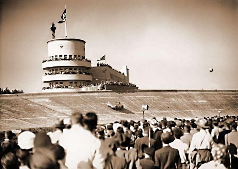Наблюдательная башня усеверного виража АФУС (архитектор— Эдмунд Мёрин). Вираж проходит будущий победитель гонки AVUS Rennen Герман Ланг зарулем 646-сильного Mercedes-Benz. Снимок 1937 года изBundesarchive-Potsdam/Wikipedia