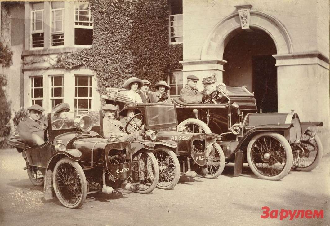 Снимок сделан упарадного имения приходского священника весной 1914 года. Автомобили Morgan уже оснащены рулевым колесом. Небольшие цилиндры, свисающие подкапотом,— глушители. Впервом изавтомобилей (модели Trial Car) сидят Гарри Морган иего жена Руфь, всоседнем— сестра Гарри Этель иеемуж Уильям Коуплэнд, авсолидном Humber 12-20HP выпуска 1911 года расположились отец Гарри— викарий Джордж Морган ссупругой Флоранс, атакже ихдочери— Дороти иФреда сосвоим будущим мужем Джорджем Хайнингсом